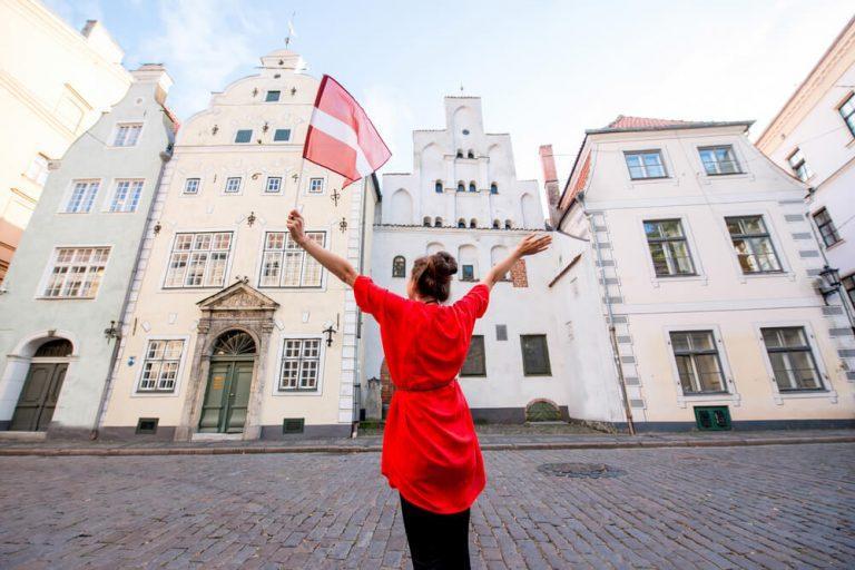 תיירת צעירה עם דגל לטביה מול שלושת האחים המפורסמים בתים עתיקים בריגה