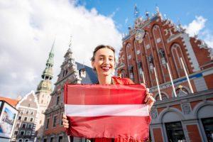 תיירת צעירה עם דגל לטביה בכיכר העיר העתיקה הראשית בריגה
